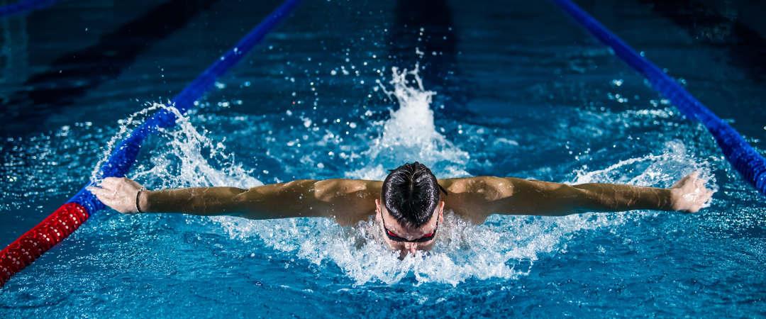 man swimming butterfly stroke in a lap pool