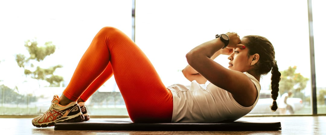 woman in orange leggings and white tank top doing abdominal exercises